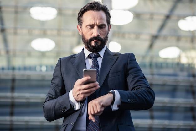 急いで。電話を持って時間をチェックする真面目なビジネスマンの腰