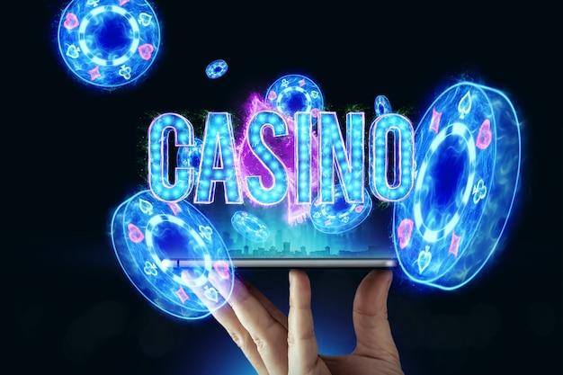 男の手にトランプのルーレットとチップ、黒ネオンの背景を持つスマートフォン。オンラインギャンブル、オンラインカジノの概念。スペースをコピーします。 3dイラスト、3dレンダリング