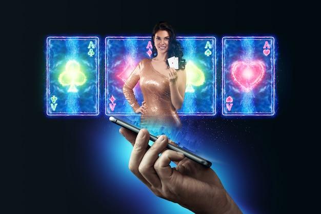 В мужской руке смартфон с игральными картами, рулеткой и фишками, крупье, красивая девушка на черно-неоновом фоне. концепция онлайн-гемблинга, онлайн-казино. скопируйте пространство.