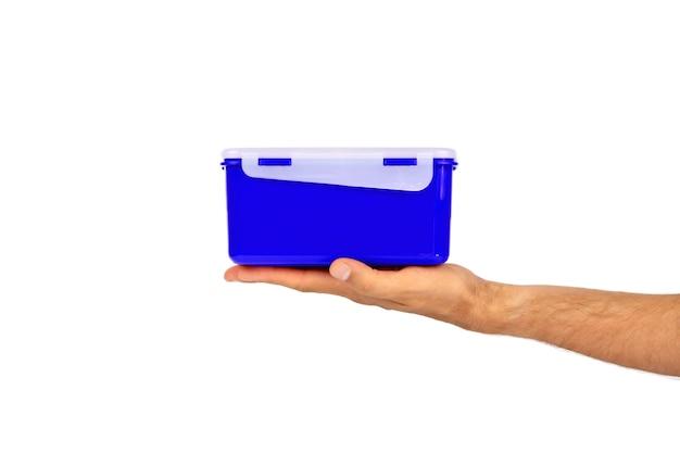 В мужской руке из эко-пластика актуального цвета ланч-бокс для быстрого и приятного обеда.