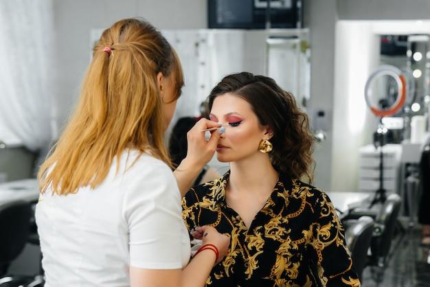 В современном салоне красоты профессиональный визажист делает макияж молодой женщине.