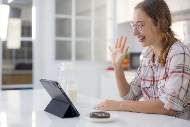 モダンなキッチンでは、ゴージャスな若い女性が健康的な朝食を食べながらデジタルタブレットを使用しています。
