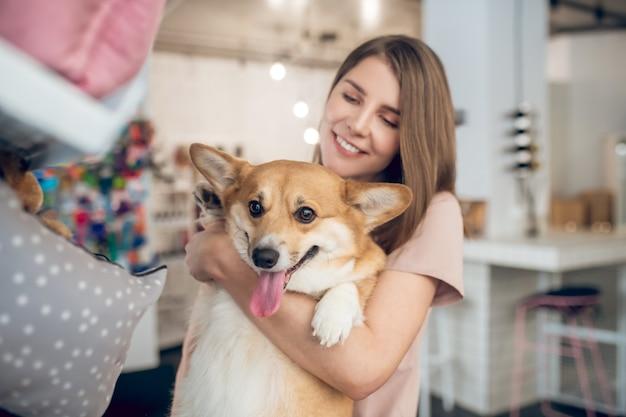 В зоомагазине. улыбающаяся девочка выбирает аксессуары для животных в зоомагазине