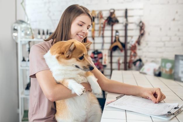 В зоомагазине. милая молодая девушка со своей собакой проводит время в зоомагазине