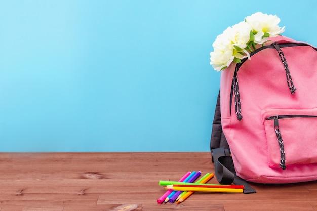 ピンクのバックパックの花、テーブルに色鉛筆、青い黒板に学校の準備、学校を開始