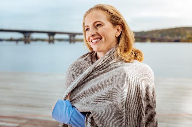 チェック柄で。水の近くを歩いている居心地の良い格子縞に包まれたインスピレーションを得た女性