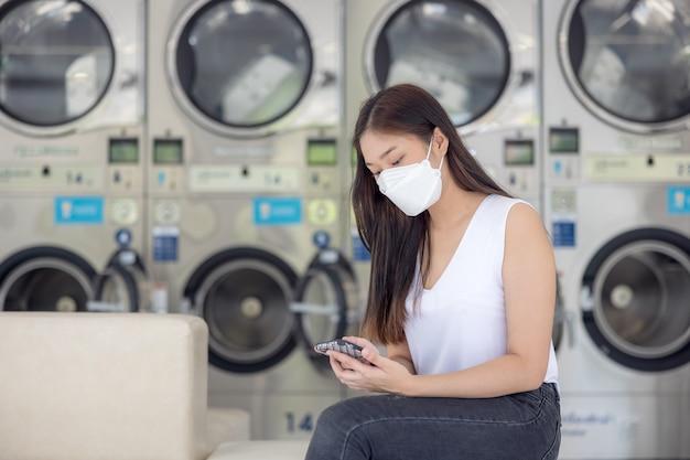 많은 자동 세탁기와 흐릿한 배경이 있는 셀프 서비스 세탁 시설에서 아시아 여성이 앉아서 프리랜서 작업을 위해 스마트폰을 사용합니다.