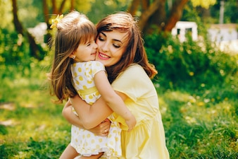 In a summer park near green trees, mom walks in a yellow dress and her little pretty girl