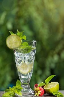 В высоком бокале освежающий напиток с добавлением мяты, лайма и льда