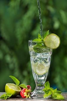 В высокий стакан со льдом и лаймом льется струя воды, рядом клубника, ломтики лайма и мяты