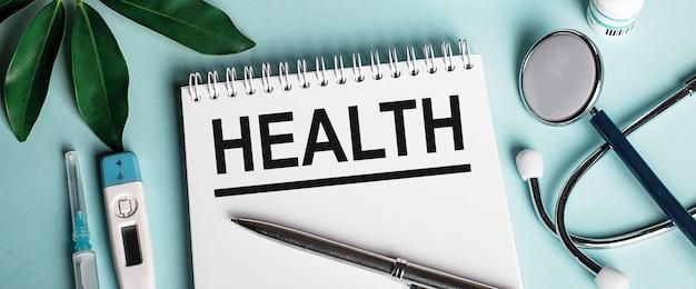 В белой записной книжке на синей поверхности возле листа шеффлеров, стетоскопа, шприца и электронного термометра написано слово здоровье
