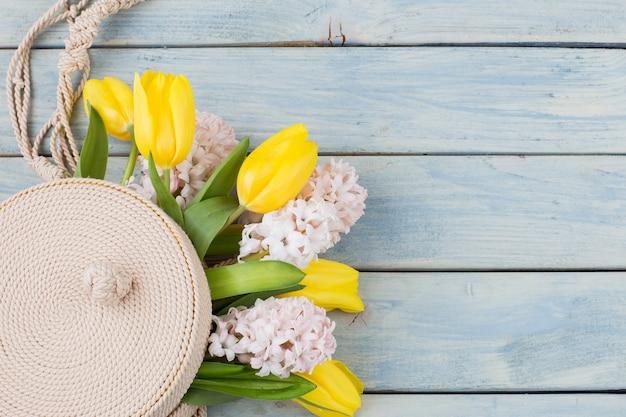 В плетеной круглой сумке букет из тюльпанов и гиацинтов