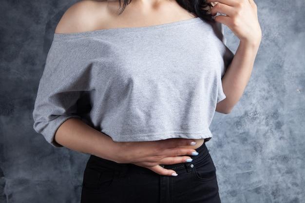 젊은 여성의 경우 회색 배경에 배가 아파요
