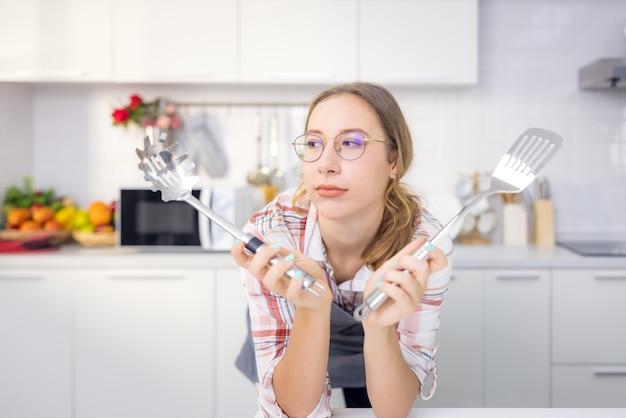 エプロンでは、笑顔の若い女性シェフの料理人が、おたまと泡立て器を持ってキッチンに立っています。