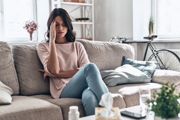 상태가 좋지 않습니다. 집에서 소파에 앉아있는 동안 두통으로 고통받는 좌절 된 젊은 여성