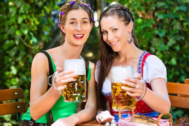 비어 가든에서 – tracht, dirndl 및 lederhosen의 여자 친구가 독일 바이에른에서 신선한 맥주를 마시고 있습니다.
