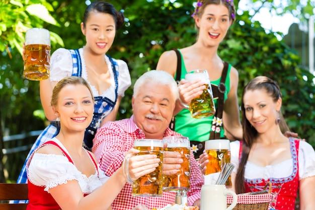 비어 가든에서-tracht, dirndl 및 lederhosen의 친구들이 독일 바이에른에서 신선한 맥주를 마시고 있습니다.