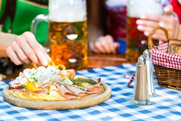 비어 가든에서-tracht, dirndl 및 lederhosen의 친구가 독일 바이에른에서 신선한 맥주를 마시 며 간식을 먹고 있습니다.