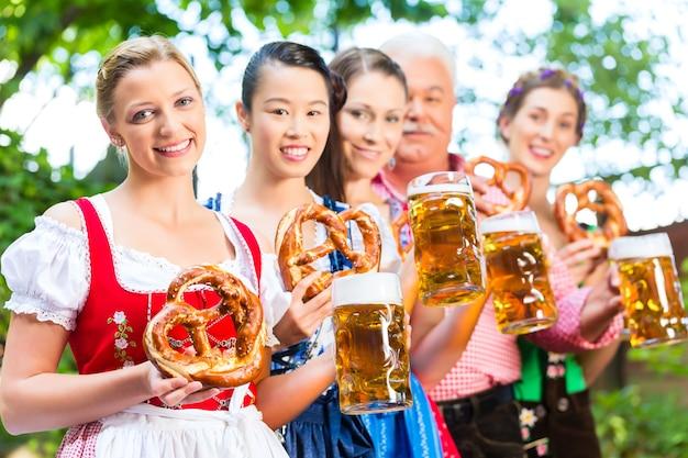 비어 가든에서-tracht, dirndl 및 lederhosen의 친구, 남녀가 독일 바이에른에서 신선한 맥주를 마시고 있습니다.