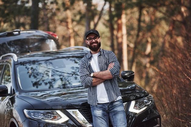 黒のアイウェア。森の中の彼の真新しい黒い車の近くのひげを生やした男。休暇の概念