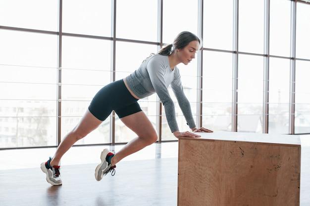 В черных шортах и серой рубашке. спортивная молодая женщина имеет фитнес-день в тренажерном зале в утреннее время
