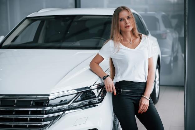 В повседневной одежде. девушка и современная машина в салоне. днем в помещении. покупка нового автомобиля.