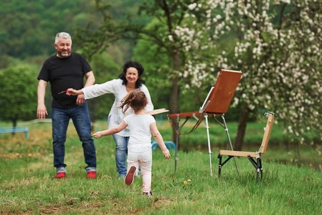 カジュアルな服装で。祖母と祖父は孫娘と屋外で楽しんでいます。絵画の構想