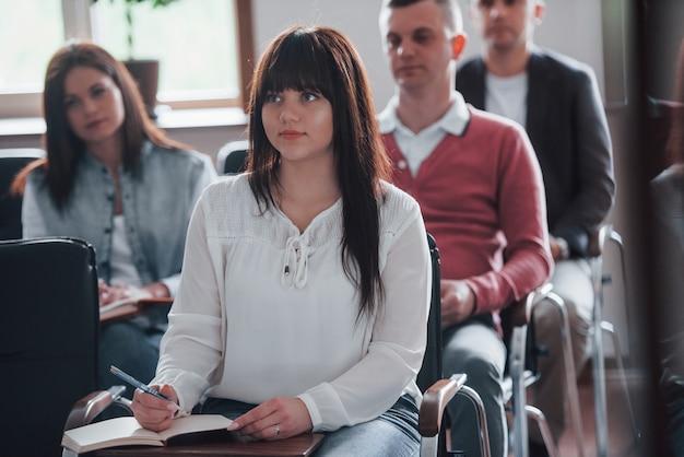 カジュアルな服装で。昼間の近代的な教室でのビジネス会議での人々のグループ