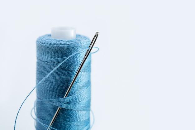 В мотке синей нити большая игла для пришивания.