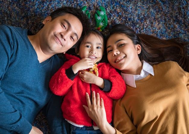 В концепции семейного праздника с декабря по январь с рождеством и новым годом. азиатская семья с дочерью родителя и ребенка, которая улыбается и смотрит в камеру, чувствует себя счастливой и веселой.
