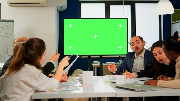 企業のオフィスの会議室には、緑色のモックアップスクリーンテレビまたは水平モードのインタラクティブデジタルホワイトボードが立っています。多民族のビジネスマンが働いて、プロのスタートアップでブレーンストーミング