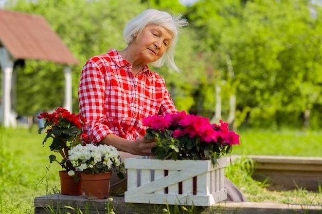 오두막집에서. 코티지 집에 살고 그녀의 꽃을 보는 동안 즐거운 느낌이 아름다운 은퇴 한 여자