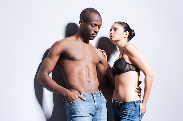 デニム風。両方が灰色の背景に立っている間、お互いに結合しているジーンズの美しい若いカップル