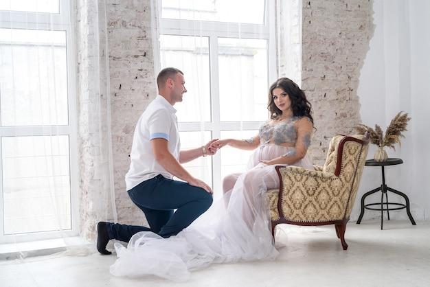 期待して。スタジオでポーズをとってファッション服で幸せな妊娠中のペア Premium写真