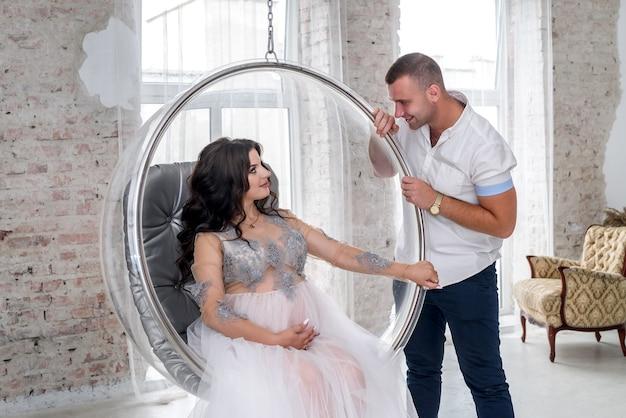 期待して。スタジオでポーズをとってファッション服で幸せな妊娠中のペア