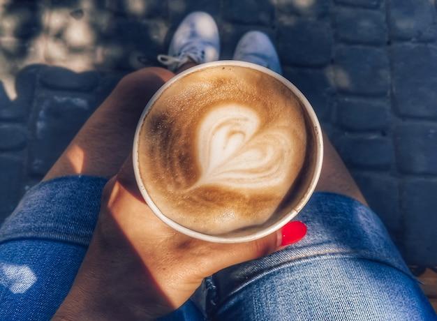 여성의 손에는 하트 모양의 거품이 든 커피가 든 종이컵이 있습니다. 음료 사진.