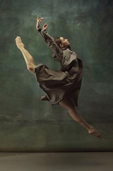 비행 중. 우아한 클래식 발레리나 춤, 어두운 스튜디오 배경에 고립 된 포즈. 스타일리시한 트렌치코트. 그레이스, 움직임, 액션 및 모션 개념. 무중력, 유연해 보입니다. 유행.