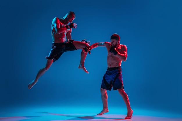 В полете. мма. два профессиональных бойца пробивают или боксируют, изолированные на синем фоне студии в неоне. подойдут мускулистые кавказские спортсмены или борющиеся боксеры. спорт, соревнования и человеческие эмоции, реклама.