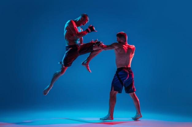 飛行中。 mma。ネオンの青いスタジオの背景に分離された2人のプロの戦闘機のパンチまたはボクシング。筋肉質の白人アスリートやボクサーの戦いにぴったりです。スポーツ、競争、人間の感情、広告。