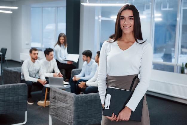 会議の前。バックグラウンドで従業員とオフィスに立っている若い女の子の肖像画