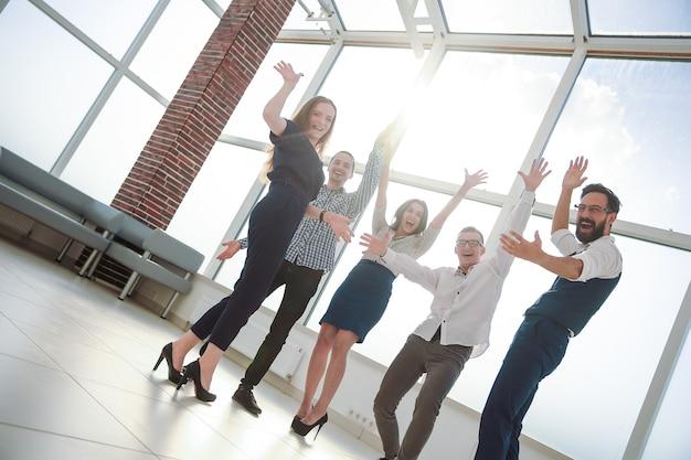 完全に成長しています。オフィスに立っている応援ビジネスチーム。成功の概念