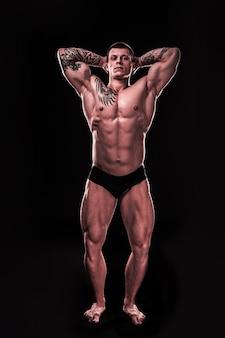 完全に成長しています。彼の膨らんだ筋肉を示すハンサムなボディービルダーの男。黒で隔離