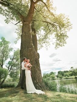В полный рост. счастливая невеста, стоя у большого старого дерева.
