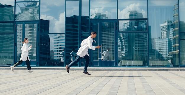 В полный рост. бегут врачи по улице города. фото с копировальным пространством.
