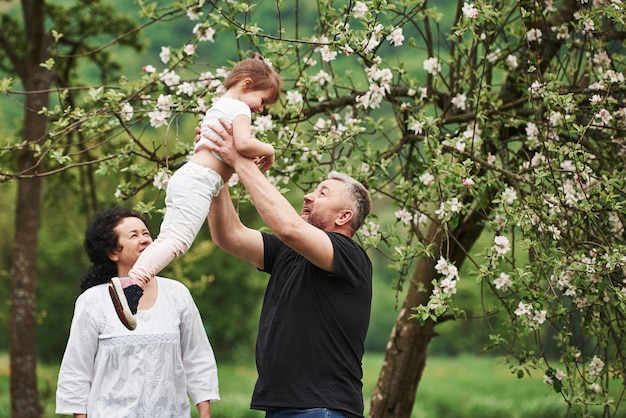 할아버지의 손에. 손녀와 함께 좋은 주말을 야외에서 즐기는 명랑 커플. 좋은 봄 날씨