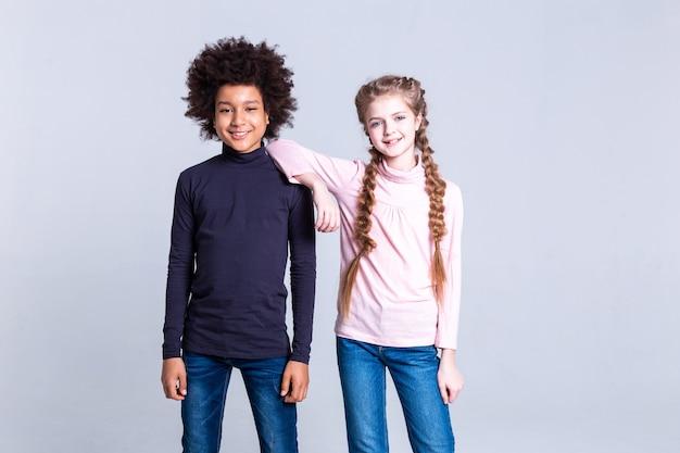 В отличном настроении. сияющая длинноволосая девушка с двумя косами опирается на плечо своего позитивного друга-афроамериканца