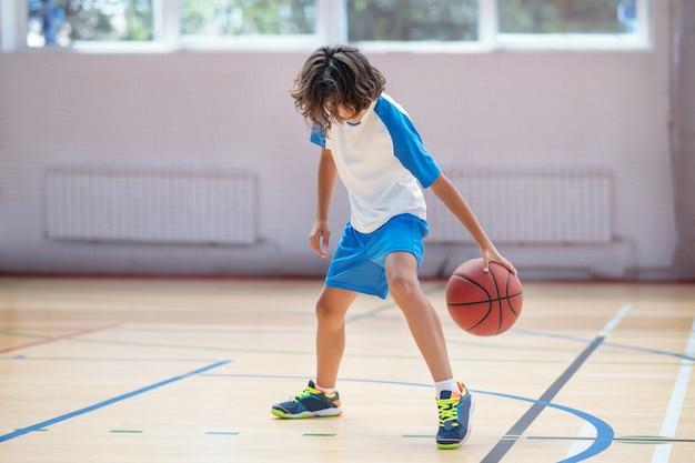 ジムで。ジムでバスケットボールのスキルをトレーニングするスポーツウェアの男子生徒