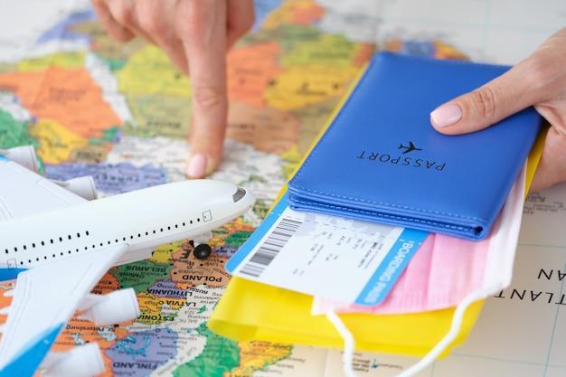 비행기 티켓과 의료 보호 마스크가 있는 여권을 손에 들고 손가락으로 국가를 가리킵니다.
