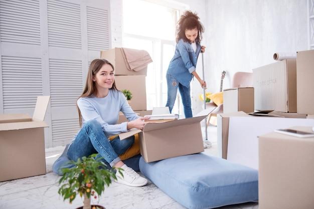 조화롭게. 상자에서 책을 꺼내고 소지품을 풀고, 룸메이트가 새 기숙사 방에서 바닥을 청소하는 즐거운 여학생