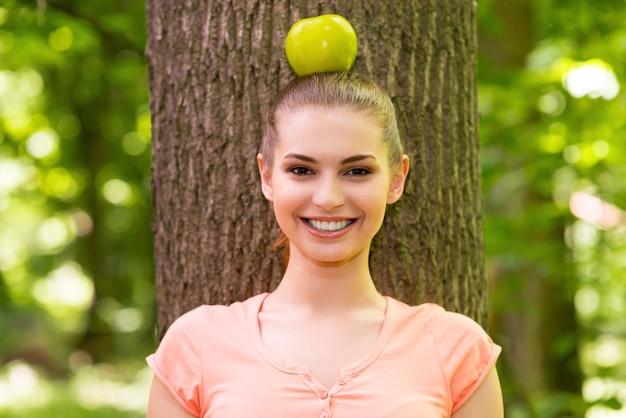자연과 조화를 이룹니다. 머리에 사과를 들고 공원에 있는 나무에 기대어 미소를 지으며 카메라를 바라보는 아름다운 젊은 여성